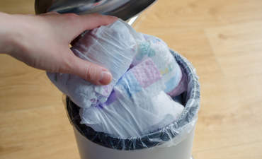 Person putting diaper in trash bin filled with more diapers