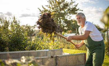 Gardener gardening in his permaculture garden, using regenerative soil farming merhods