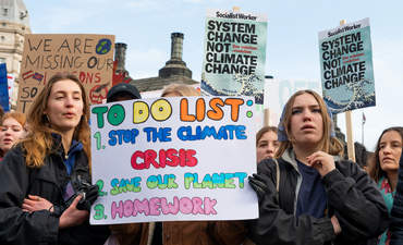 Student activists with placards at the February 2020 Youth Strike 4 Climate demonstration rally at Parliament Square, in protest of the government's lack of action on climate change in the U.K.