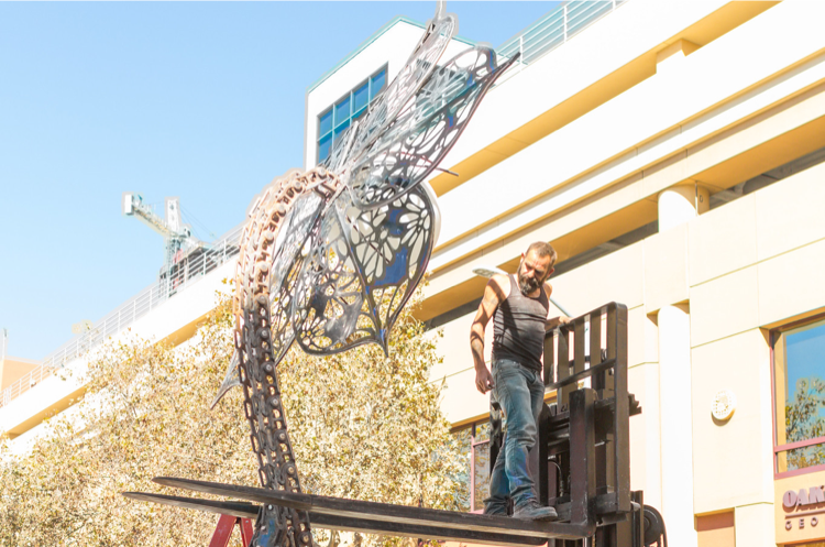 Metal flower statue getting installed using forklift